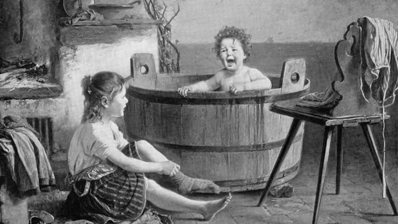Un enfant prend son bain dans une bassine